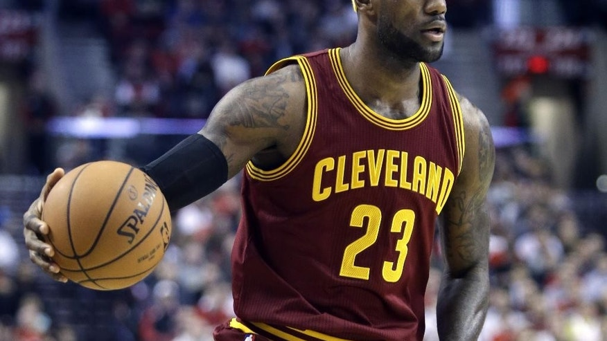 Cleveland Cavaliers forward LeBron James dribbles down court during the first half of an NBA basketball game against the Portland Trail Blazers in Portland, Ore., Tuesday, Nov. 4, 2014.(AP Photo/Don Ryan)