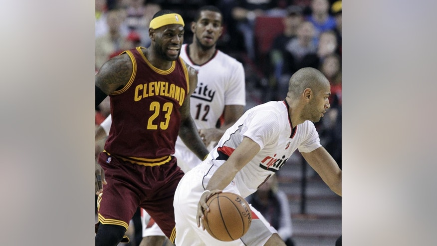 Portland Trail Blazers forward Nicolas Batum, from France, right, drives past Cleveland Cavaliers forward LeBron James during the first half of an NBA basketball game in Portland, Ore., Tuesday, Nov. 4, 2014.(AP Photo/Don Ryan)