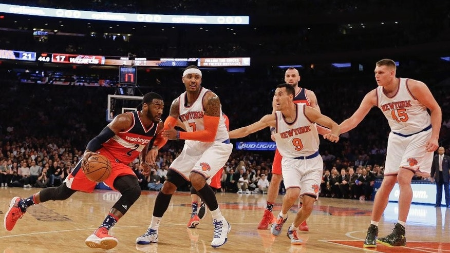 Washington Wizards' John Wall (2) drives past New York Knicks' Carmelo Anthony (7), Pablo Prigioni (9), and Cole Aldrich (45) during the first half of an NBA basketball game Tuesday, Nov. 4, 2014, in New York. (AP Photo/Frank Franklin II)
