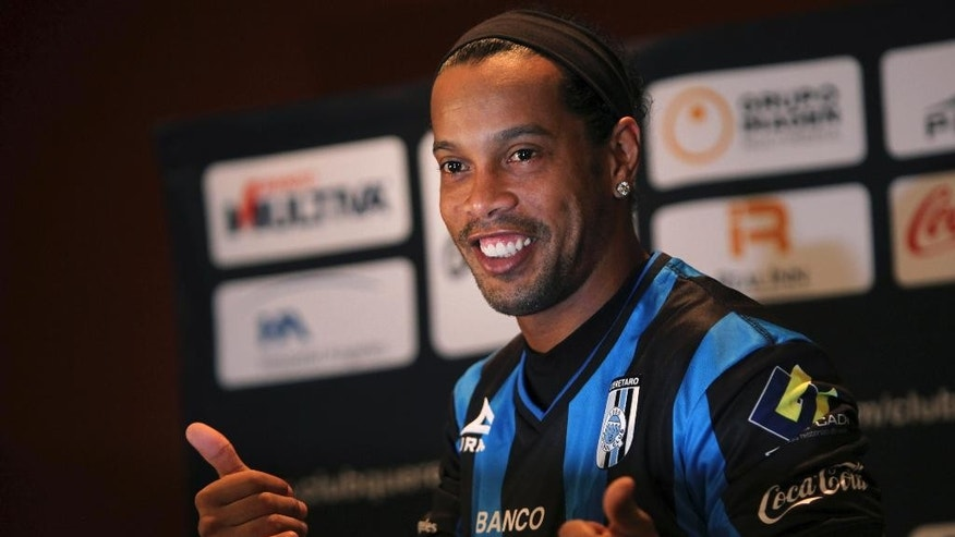 FILE - In this Sept. 12, 2014 file photo, Brazil's Ronaldinho poses for a photo after slipping on his new Queretaro soccer club jersey at a press conference in Mexico City. Mexican first-division club Queretaro signed the former 34-year-old soccer star, who had been without a club since leaving Brazil's Atletico Mineiro in July and had been negotiating with several clubs. The upbeat mood of his signing didn't last long. Even before he had played his first match, Ronaldinho became the subject of a racist attack _ the kind that have become common with black football players across Europe. (AP Photo/Marco Ugarte)