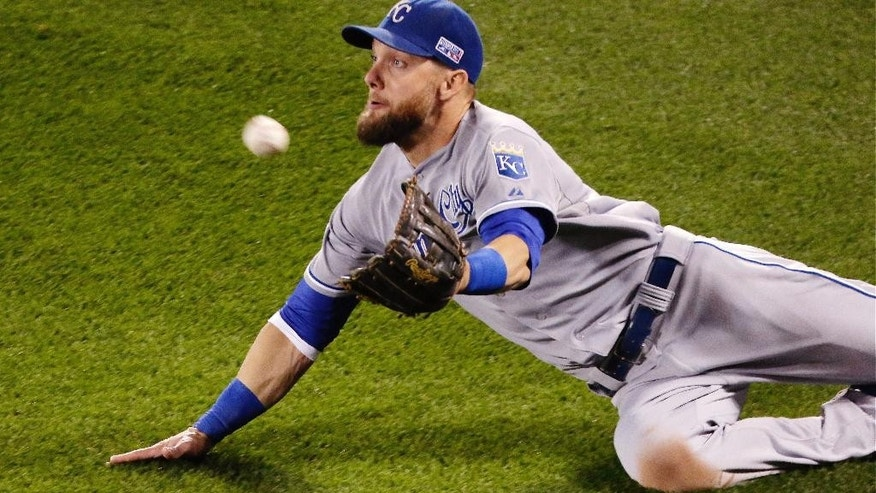 FILE - In this Oct. 10, 2014, file photo, Kansas City Royals' Alex Gordon makes diving catch on a ball hit by Baltimore Orioles' Steve Pearce for an out during Game 1 of the American League baseball championship series in Baltimore. Gordon was one of three Royals named Gold Glove winners Tuesday, Nov. 4. (AP Photo/Charlie Riedel, File)
