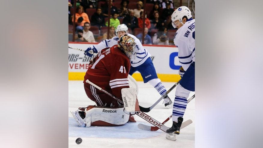Arizona Coyotes goalie Mike Smith (41) makes the save agaiinst the Toronto Maple Leafs in the first periiod during an NHL hockey game, Tuesday, Nov. 4, 2014, in Glendale, Ariz.  Maple Leafs James Van Riemsdyk is at right. (AP Photo/Rick Scuteri)