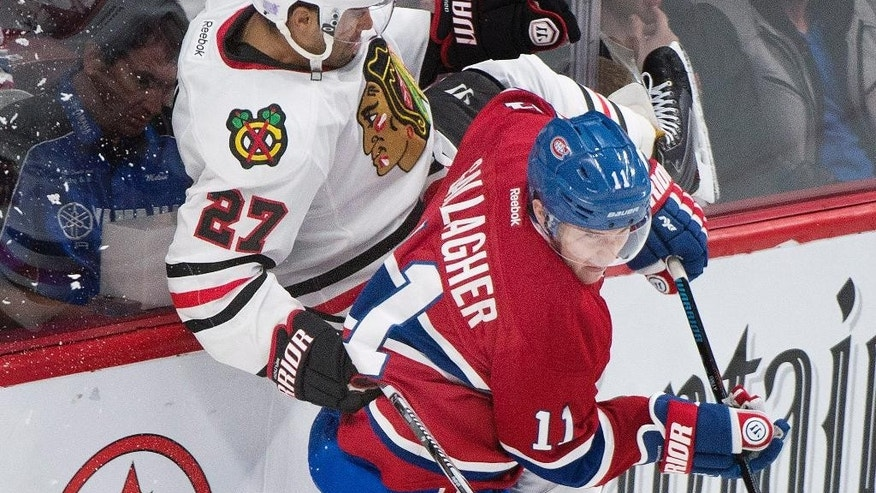 Chicago Blackhawks' Johnny Oduya (27) collides with Montreal Canadiens' Brendan Gallagher during the third period of an NHL hockey game, Tuesday, Nov. 4, 2014 in Montreal.  (AP Photo/The Canadian Press, Graham Hughes)