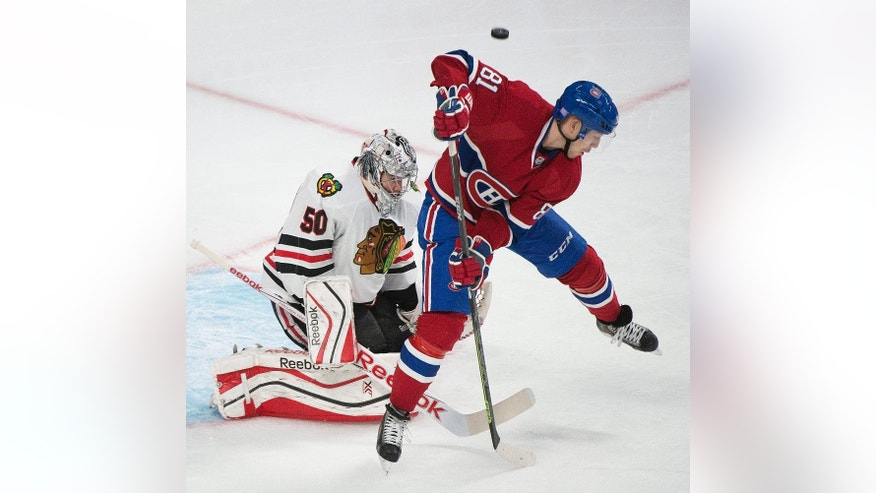 Chicago Blackhawks goaltender Corey Crawford makes a save against Montreal Canadiens' Lars Eller during the first period of an NHL hockey game, Tuesday, Nov. 4, 2014 in Montreal.  (AP Photo/The Canadian Press, Graham Hughes)
