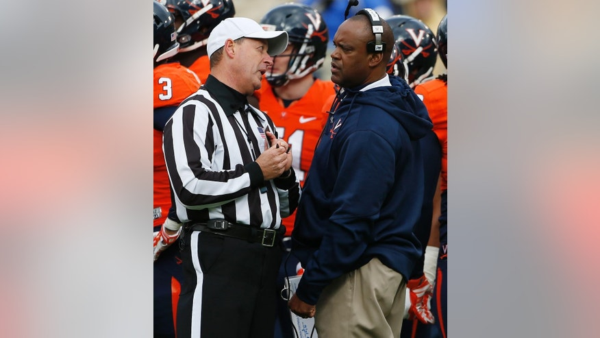 Virginia head coach Mike London speaks with an official during the first half of an NCAA college football game against Georgia Tech, Saturday, Nov. 1, 2014, in Atlanta. (AP Photo/Mike Stewart)
