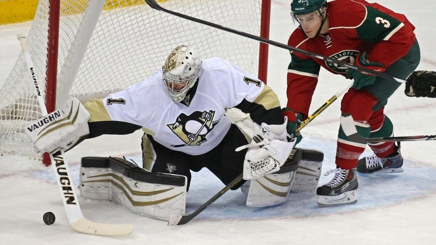 Pittsburgh Penguins goalie Thomas Greiss, of Germany, blocks a shot as Minnesota Wild's Charlie Coyle looks for a rebound during the first period of an NHL hockey game, Tuesday, Nov. 4, 2014, in St. Paul, Minn. (AP Photo/Bruce Bisping)