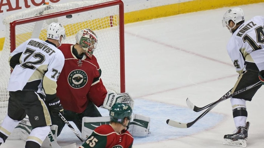 Minnesota Wild goalie Darcy Kuemper defends as Pittsburgh Penguins' Chris Kunitz, right, scores a power-play goal during the second period of an NHL hockey game, Tuesday, Nov. 4, 2014 in St. Paul, Minn. Pittsburgh won 4-1. (AP Photo/Bruce Bisping)