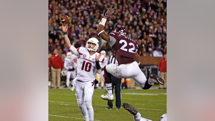 Arkansas quarterback Brandon Allen (10) is pressured by Mississippi State linebacker Matthew Wells (22) into throwing an interception in the second half of an NCAA college football game in Starkville, Miss., Saturday, Nov. 1, 2014. No. 1 Mississippi State won 17-10. (AP Photo/Rogelio V. Solis)