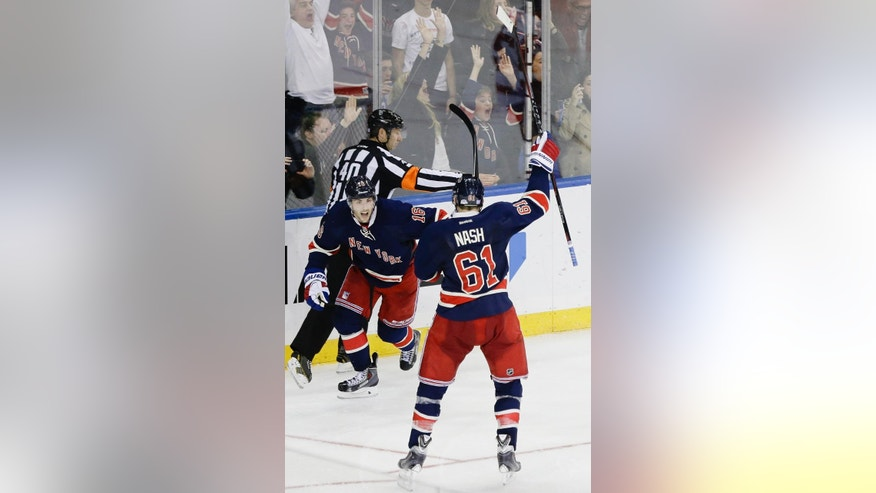 New York Rangers' Derick Brassard (16) celebrates with Rick Nash (61) after scoring a goal to win the game during the overtime period of an NHL hockey game against the Detroit Red Wings Wednesday, Nov. 5, 2014, in New York. The Rangers won the game 4-3. (AP Photo/Frank Franklin II)
