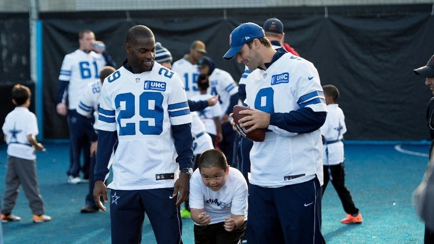 Dallas Cowboys' quarterback Tony Romo, right, and running back DeMarco Murray meet children from Wembley Primary School for a Dallas Cowboys community day Play 60 event outside Wembley Stadium in London, England, Tuesday Nov. 4, 2014. The Dallas Cowboys will play the Jacksonville Jaguars in an NFL football game at Wembley Stadium on Sunday Nov. 9 (AP Photo/Tim Ireland)