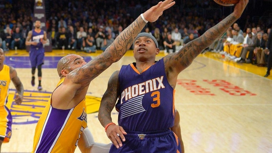 Phoenix Suns guard Isaiah Thomas shoots as Los Angeles Lakers forward Carlos Boozer defends during the first half of an NBA basketball game, Tuesday, Nov. 4, 2014, in Los Angeles.(AP Photo/Mark J. Terrill)