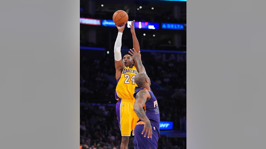 Los Angeles Lakers guard Kobe Bryant shoots as Phoenix Suns forward P.J. Tucker defends during the first half of an NBA basketball game, Tuesday, Nov. 4, 2014, in Los Angeles .(AP Photo/Mark J. Terrill)