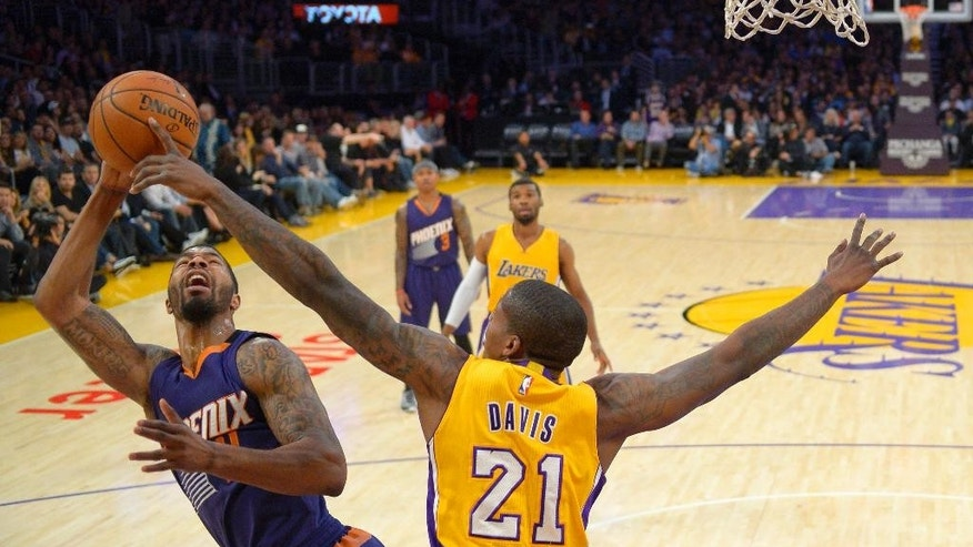 Phoenix Suns forward Markieff Morris, left, tries to shoot while Los Angeles Lakers forward Ed Davis defends during the first half of an NBA basketball game, Tuesday, Nov. 4, 2014, in Los Angeles.(AP Photo/Mark J. Terrill)