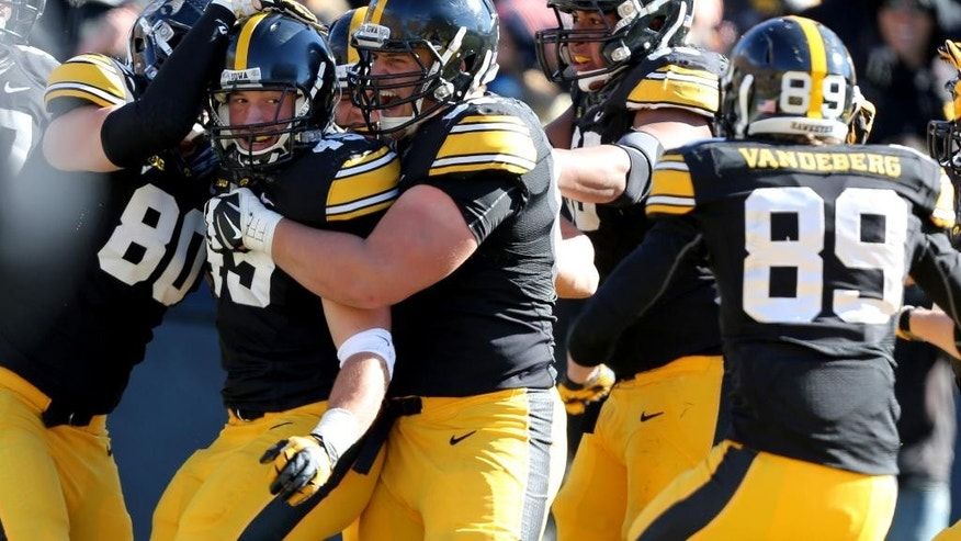 Iowa running back Mark Weisman (45) is mobbed by his teammates after scoring a touchdown during the first half of an NCAA college football game against Northwestern, Saturday, Nov. 1, 2014, in Iowa City, Iowa. Iowa won 48-7. (Justin Hayworth/AP Photo)