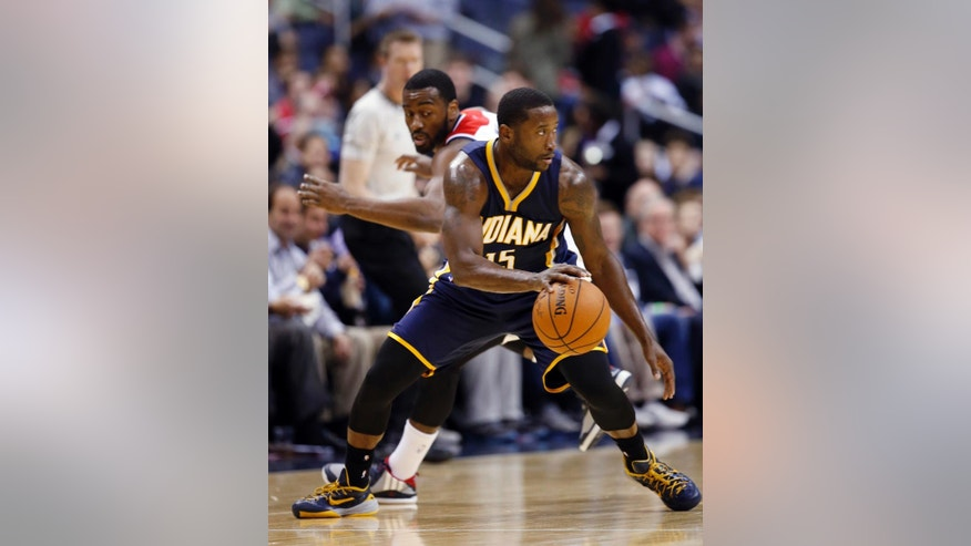 Indiana Pacers guard Donald Sloan (15) dribbles away from Washington Wizards guard John Wall (2) during the first half of an NBA basketball game, Wednesday, Nov. 5, 2014, in Washington. (AP Photo/Alex Brandon)