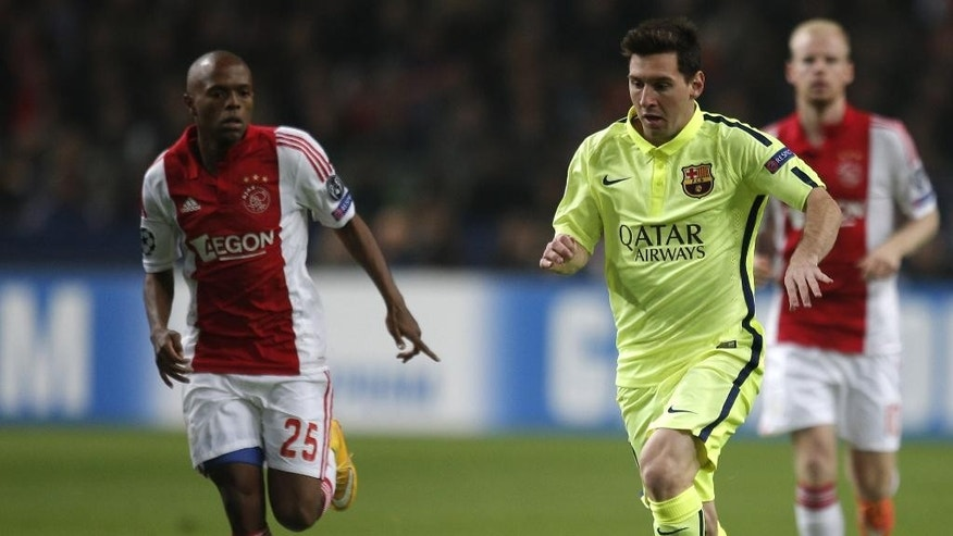 Barcelona's Lionel Messi vies for the ball with Ajax's Thulani Serero, left, during the Group F Champions League match between AFC Ajax and FC Barcelona at ArenA stadium in Amsterdam, Netherlands, Wednesday, Nov. 5, 2014. (AP Photo/Peter Dejong)