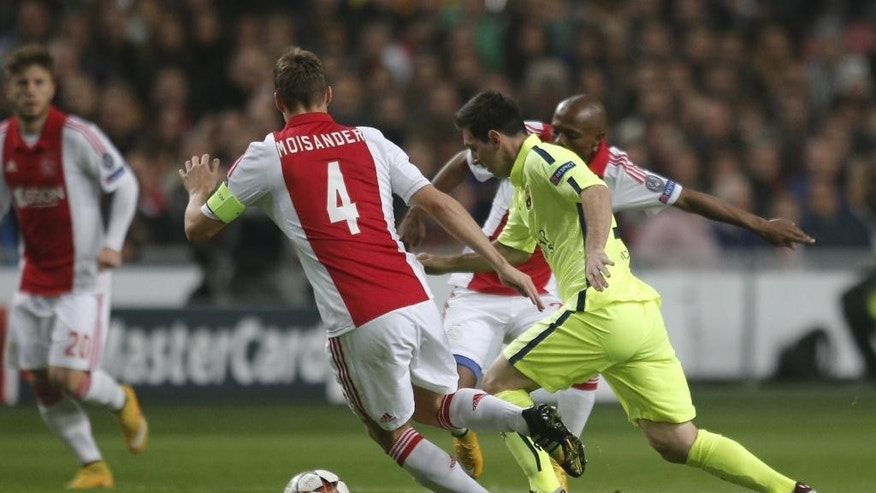 Barcelona's Lionel Messi vies for the ball with Ajax's Niklas Moisander, left, during the Group F Champions League match between AFC Ajax and FC Barcelona at ArenA stadium in Amsterdam, Netherlands, Wednesday, Nov. 5, 2014. (AP Photo/Peter Dejong)