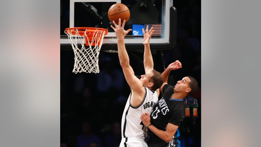 Minnesota Timberwolves guard Kevin Martin (23) defends as Brooklyn Nets forward Bojan Bogdanovic goes up for a layup in the first half of an NBA basketball game, Wednesday, Nov. 5, 2014, in New York. (AP Photo/Kathy Willens)