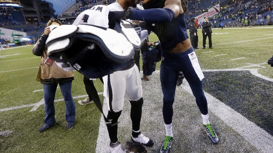 Seattle Seahawks' Richard Sherman, right, trades jerseys with Oakland Raiders' Charles Woodson after an NFL football game, Sunday, Nov. 2, 2014, in Seattle. The Seahawks won 30-24. (AP Photo/Elaine Thompson)