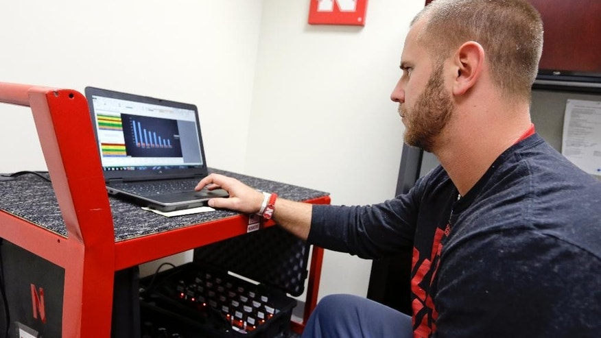 Nebraska assistant strength coach Ben Schumacher downloads to his laptop in Lincoln, Neb., Tuesday, Oct. 28, 2014, data on football players obtained from Catapult GPS devices that track their movements and exertion during practice. At Nebraska, the top 50 football players slip a monitor weighing about 3 ounces into a pouch in the back of the tight-fit shirts they wear under their shoulder pads. (AP Photo/Nati Harnik)
