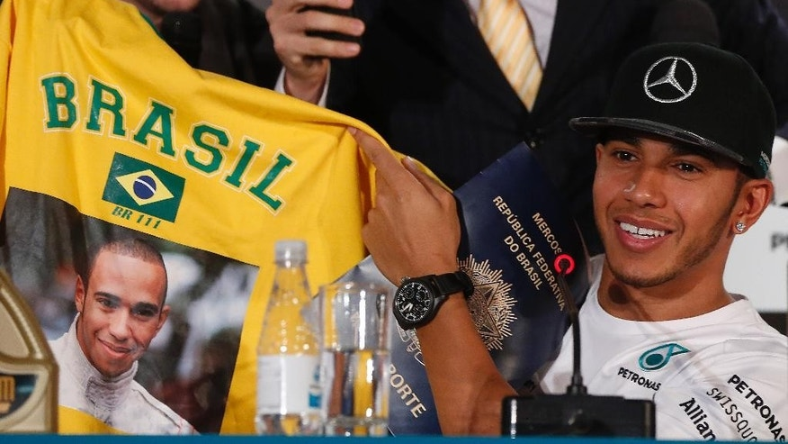 Mercedes driver Lewis Hamilton of Britain holds a national Brazilian jersey designed with his image, given to him by  TV comedians, during a press conference in Sao Paulo, Brazil, Wednesday, Nov. 5, 2014. Hamilton will compete Sunday in the Brazilian Formula One Grand Prix at Sao Paulo's Interlagos circuit. (AP Photo/Andre Penner)