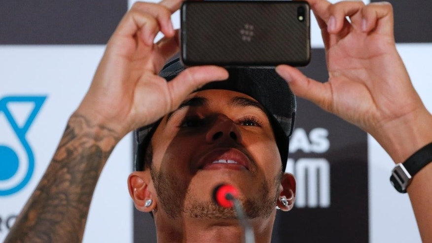 Mercedes driver Lewis Hamilton of Britain takes a photo as he attends a press conference in Sao Paulo, Brazil, Wednesday, Nov. 5, 2014. Hamilton will compete Sunday in the Brazilian Formula One Grand Prix at Sao Paulo's Interlagos circuit. (AP Photo/Andre Penner)