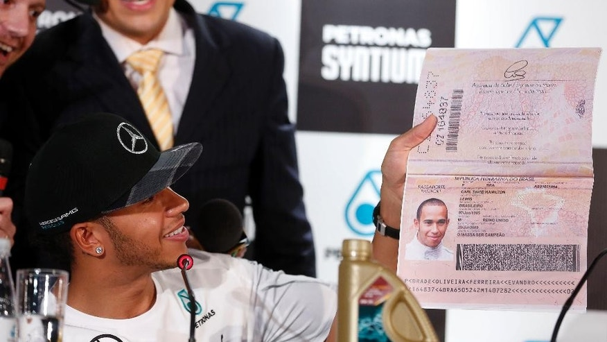 Mercedes driver Lewis Hamilton of Britain holds up an oversized, mock Brazilian passport, given to him by TV comedians during a press conference in Sao Paulo, Brazil, Wednesday, Nov. 5, 2014. Hamilton will compete Sunday in the Brazilian Formula One Grand Prix at Sao Paulo's Interlagos circuit. (AP Photo/Andre Penner)