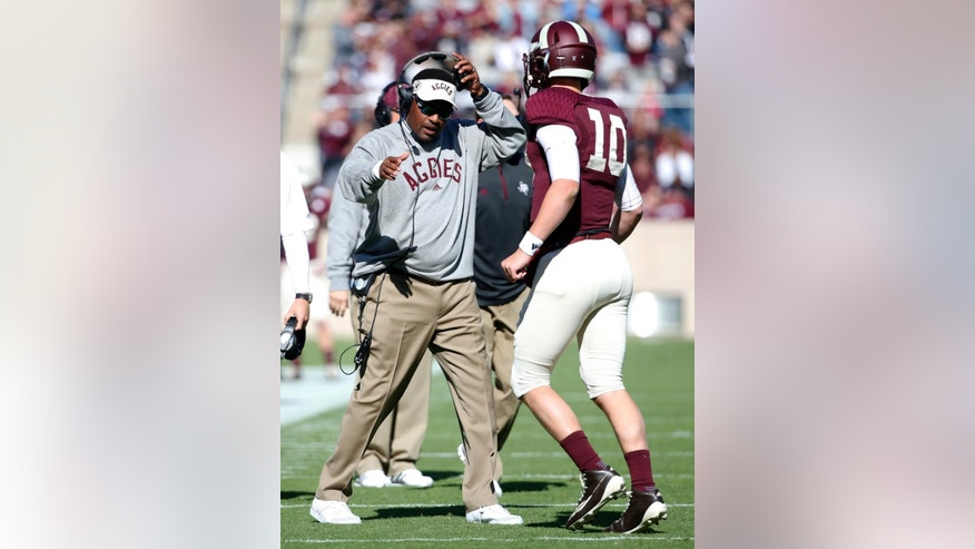 Texas A&M head coach Kevin Sumlin, left, greets quarterback Kyle Allen (10) at the sideline after the Aggies scored against Louisiana Monroe in the first half of an NCAA college football game, Saturday, Nov. 1, 2014, in College Station, Texas. (AP Photo/Tony Gutierrez)