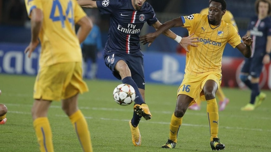PSG's Javier Pastore, center, is challenged by APOEL's De Oliveira, right, during the Champions League Group F soccer match between Paris Saint Germain and Apoel at Parc des Princes stadium in Paris, France, Wednesday, Nov. 5, 2014. (AP Photo/Francois Mori)