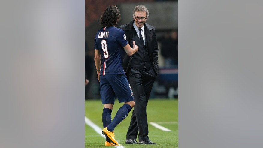 PSG's Edinson Cavani and PSG's head coach Laurent Blanc, right, celebrate their victory after the Champions League Group F soccer match between Paris Saint Germain and Apoel at the Parc des Princes stadium in Paris, France, Wednesday, Nov. 5, 2014. PSG won 1-0. (AP Photo/Christophe Ena)