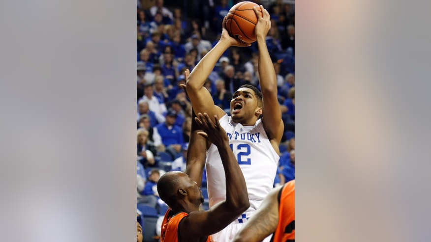 FILE - In this Nov. 2, 2014, file photo, Kentucky's Karl-Anthony Towns shoots over Pikeville's Michael Eneh during the first half of an NCAA college basketball exhibition game in Lexington, Ky. The 6-11 Towns, a three-time All-State player in New Jersey, and 6-10 Trey Lyles, whose made the game-winning free throw in his final prep game to clinch an Indiana state title, both averaged more than 20 points and about 13 rebounds a game as high school seniors. (AP Photo/James Crisp, File)