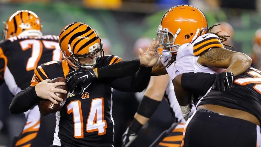 Cincinnati Bengals quarterback Andy Dalton (14) is pressured by Cleveland Browns outside linebacker Jabaal Sheard during the first half of an NFL football game Thursday, Nov. 6, 2014, in Cincinnati. (AP Photo/Michael Conroy)