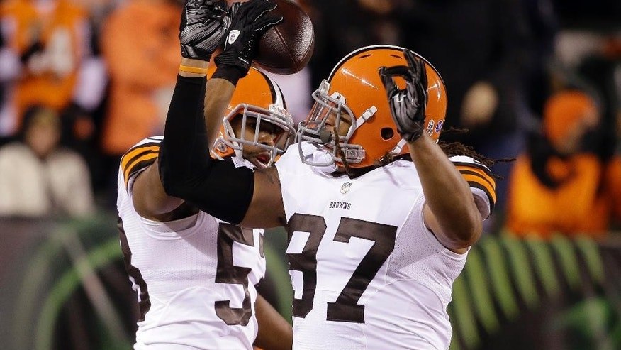 Cleveland Browns inside linebacker Craig Robertson (53) celebrates with Jabaal Sheard (97) after Robertson intercepted a pass during the first half of an NFL football game against the Cincinnati Bengals on Thursday, Nov. 6, 2014, in Cincinnati. (AP Photo/Darron Cummings)