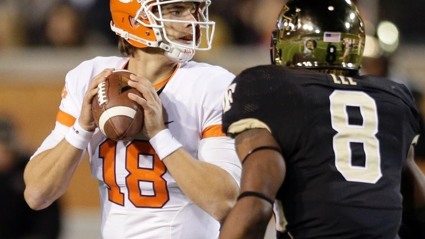 Clemson's Cole Stoudt (18) looks to pass as Wake Forest's Marquel Lee (8) closes in during the first half of an NCAA college football game in Winston-Salem, N.C., Thursday, Nov. 6, 2014. (AP Photo/Chuck Burton)