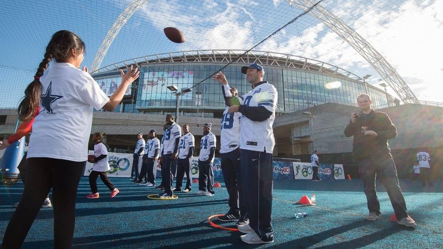 Dallas Cowboys quarterback Tony Romo throws a football to a local school child during a community day event outside Wembley Stadium in London, England, Tuesday Nov. 4, 2014. The Dallas Cowboys will play the Jacksonville Jaguars in an NFL football game at Wembley Stadium on Sunday Nov. 9 (AP Photo/Tim Ireland)