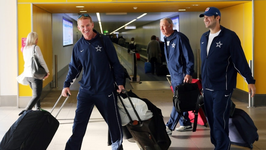 Dallas Cowboys head coach Jason Garrett, left, and quarterback Tony Romo arrives at Gatwick Airport, England, Tuesday Nov. 4, 2014 prior to the NFL international series match between the Jacksonville Jaguars and Dallas Cowboys at Wembley Stadium on Sunday. (AP Photo/NFL UK, Dave Shopland)