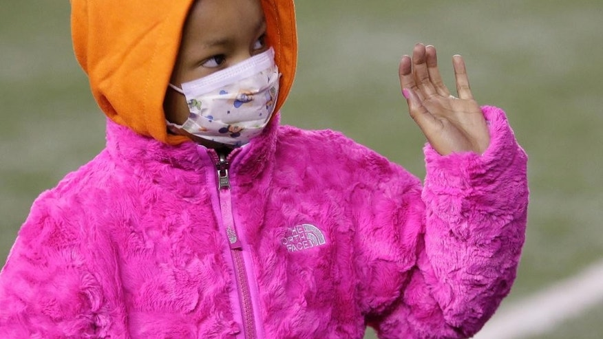 Leah Still waves during a ceremony in the first half of an NFL football game between the Cincinnati Bengals and the Cleveland Browns on Thursday, Nov. 6, 2014, in Cincinnati. Leah, who is battling cancer, was watching her father, Cincinnati Bengals defensive tackle Devon Still, play for the first time. (AP Photo/AJ Mast)