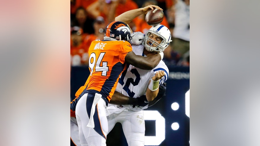 FILE - In this Sept. 7, 2014, file photo, Indianapolis Colts quarterback Andrew Luck (12) is sacked by Denver Broncos defensive end DeMarcus Ware (94) during the first half of an NFL football game in Denver. (AP Photo/Jack Dempsey, File)