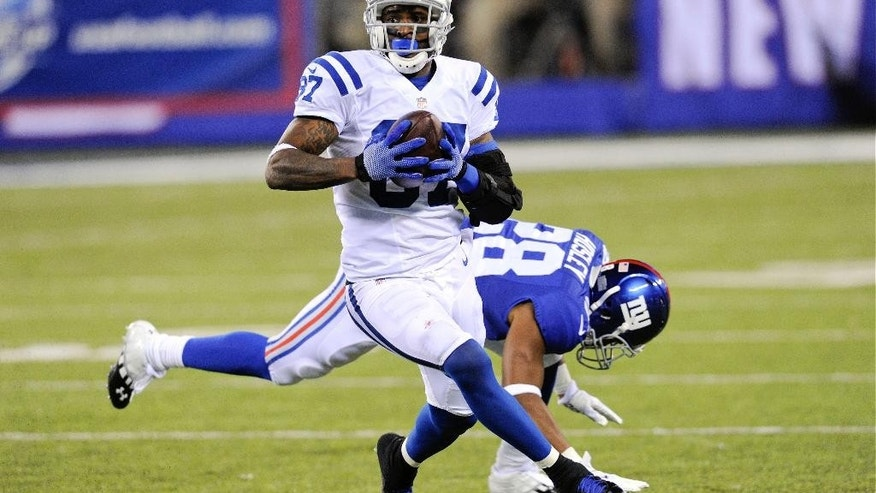 Indianapolis Colts wide receiver Reggie Wayne (87) runs away from New York Giants' Jayron Hosley (28) for a touchdown during the second half of an NFL football game Monday, Nov. 3, 2014, in East Rutherford, N.J. (AP Photo/Bill Kostroun)