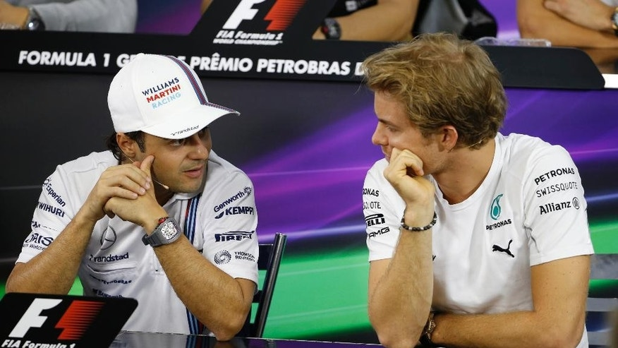 Mercedes driver Nico Rosberg of Germany, right, talks with Williams driver Felipe Massa of Brazil during a press conference in Sao Paulo, Brazil, Thursday, Nov. 6, 2014. Rosberg knows he will need some help to overcome Mercedes teammate Lewis Hamilton for the Formula One title. The Brazilian Grand Prix may be where he gets some.  (AP Photo/Andre Penner)