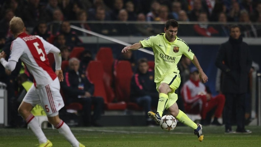 Barcelona's Lionel Messi tries to beat Ajax's goalkeeper Jasper Cillessen during the Group F Champions League match between AFC Ajax and FC Barcelona at ArenA stadium in Amsterdam, Netherlands, Wednesday, Nov. 5, 2014. (AP Photo/Peter Dejong)