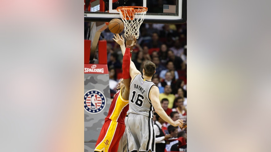 San Antonio Spurs center Aaron Baynes (16) and Houston Rockets center Dwight Howard go up for a rebound during the second quarter of an NBA basketball game, Thursday, Nov. 6, 2014, in Houston. (AP Photo/Patric Schneider)