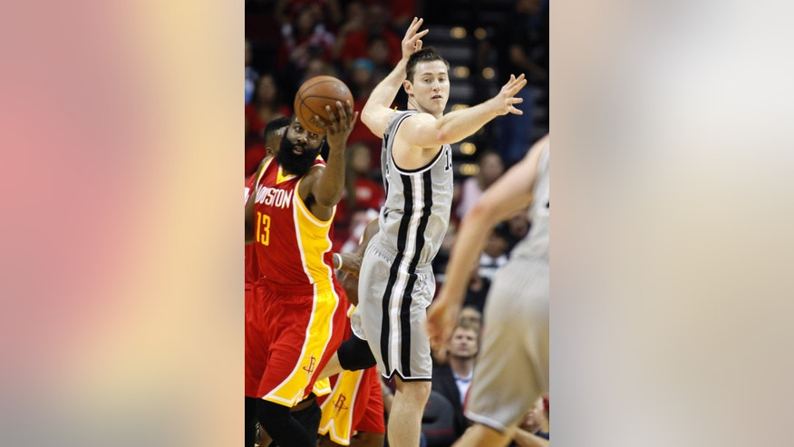 Houston Rockets guard James Harden (13) keeps a rebound away from San Antonio Spurs center Aaron Baynes during the first quarter of an NBA basketball game, Thursday, Nov. 6, 2014, in Houston. (AP Photo/Patric Schneider)