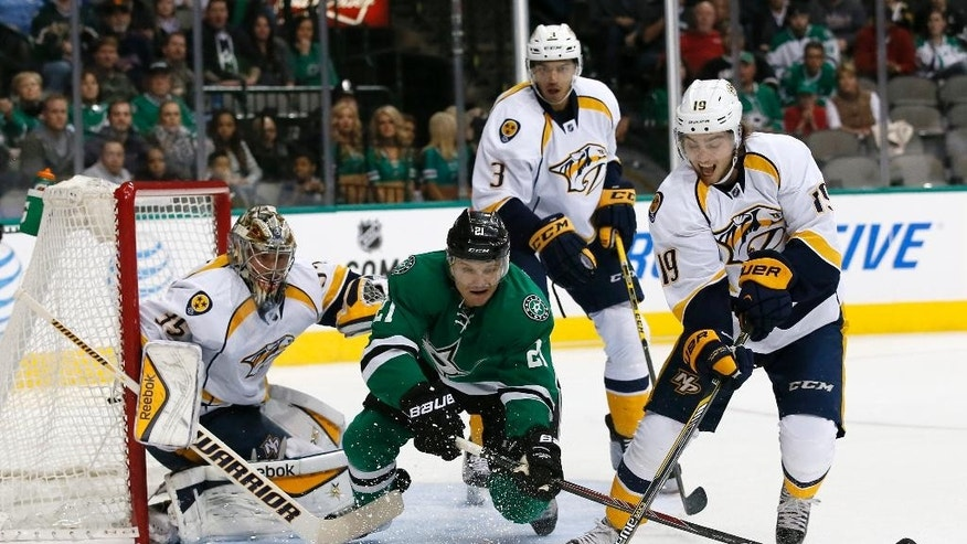 Dallas Stars left wing Antoine Roussel (21) fights for control of a loose puck against Nashville Predators center Calle Jarnkrok (19), as defenseman Seth Jones (3) and goalie Pekka Rinne (35) of Finland watch during the first period of an NHL hockey game, Thursday, Nov. 6, 2014, in Dallas. (AP Photo/Tony Gutierrez)