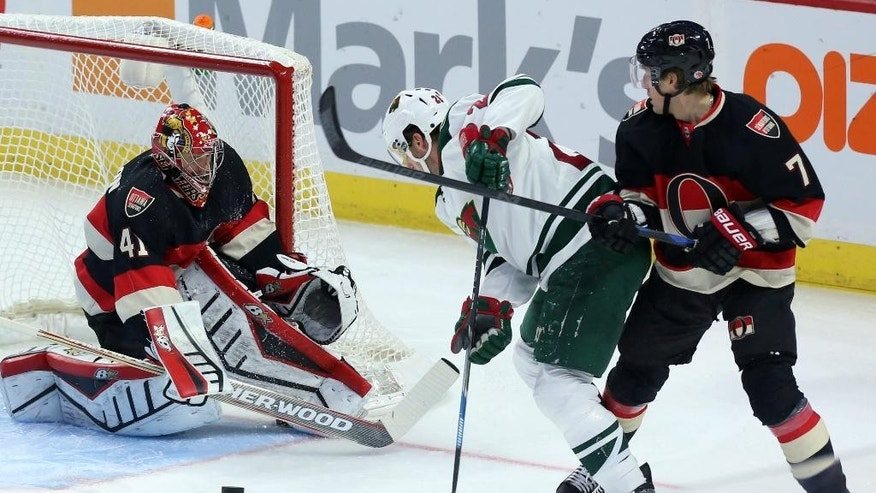 Ottawa Senators' Kyle Turris, right, checks Minnesota Wild's Thomas Vanek (26) as Senators goaltender Craig Anderson (41) attempts to reach a loose puck during first-period NHL hockey game action in Ottawa, Ontario, Thursday, Nov. 6, 2014. (AP Photo/The Canadian Press, Fred Chartrand)