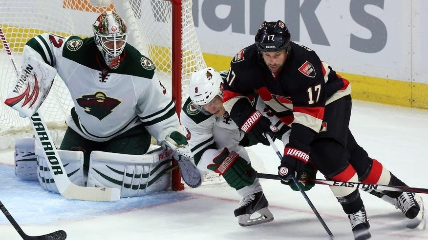 Ottawa Senators' David Legwand (17) and Minnesota Wild's Mikko Koivu (9) battle for the puck as Wild goaltender Niklas Backstrom (32) looks on during second-period NHL hockey game action in Ottawa, Ontario, Thursday, Nov. 6, 2014. (AP Photo/The Canadian Press, Fred Chartrand)