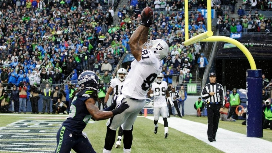 Oakland Raiders tight end Mychal Rivera, right, catches a pass for a touchdown above Seattle Seahawks cornerback Richard Sherman, left, in the second half of an NFL football game, Sunday, Nov. 2, 2014, in Seattle. (AP Photo/Stephen Brashear)