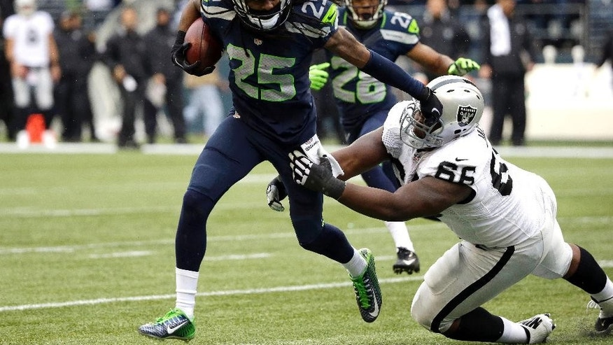 Seattle Seahawks cornerback Richard Sherman (25) pushes aside Oakland Raiders' Gabe Jackson after Sherman made an interception in the first half of an NFL football game, Sunday, Nov. 2, 2014, in Seattle. (AP Photo/Elaine Thompson)