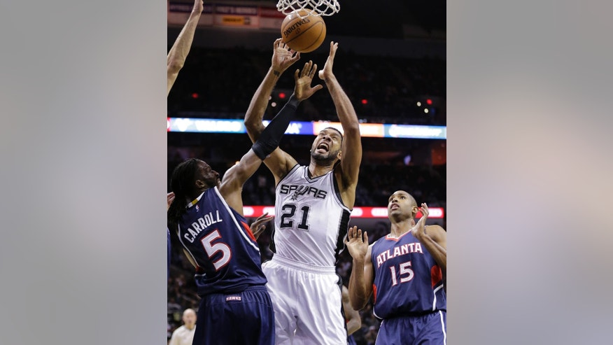 San Antonio Spurs' Tim Duncan (21) is fouled by Atlanta Hawks' DeMarre Carroll (5) as he tries to score during the second half of an NBA basketball game, Wednesday, Nov. 5, 2014, in San Antonio. San Antonio won 94-92. (AP Photo/Eric Gay)