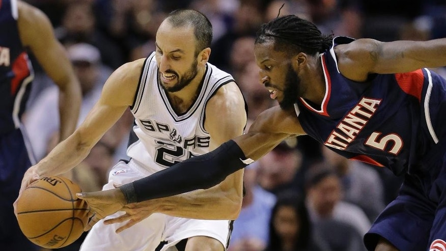 San Antonio Spurs' Manu Ginobili (20) and Atlanta Hawks' DeMarre Carroll (5) fight for a loose ball during the second half of an NBA basketball game, Wednesday, Nov. 5, 2014, in San Antonio. San Antonio won 94-92. (AP Photo/Eric Gay)